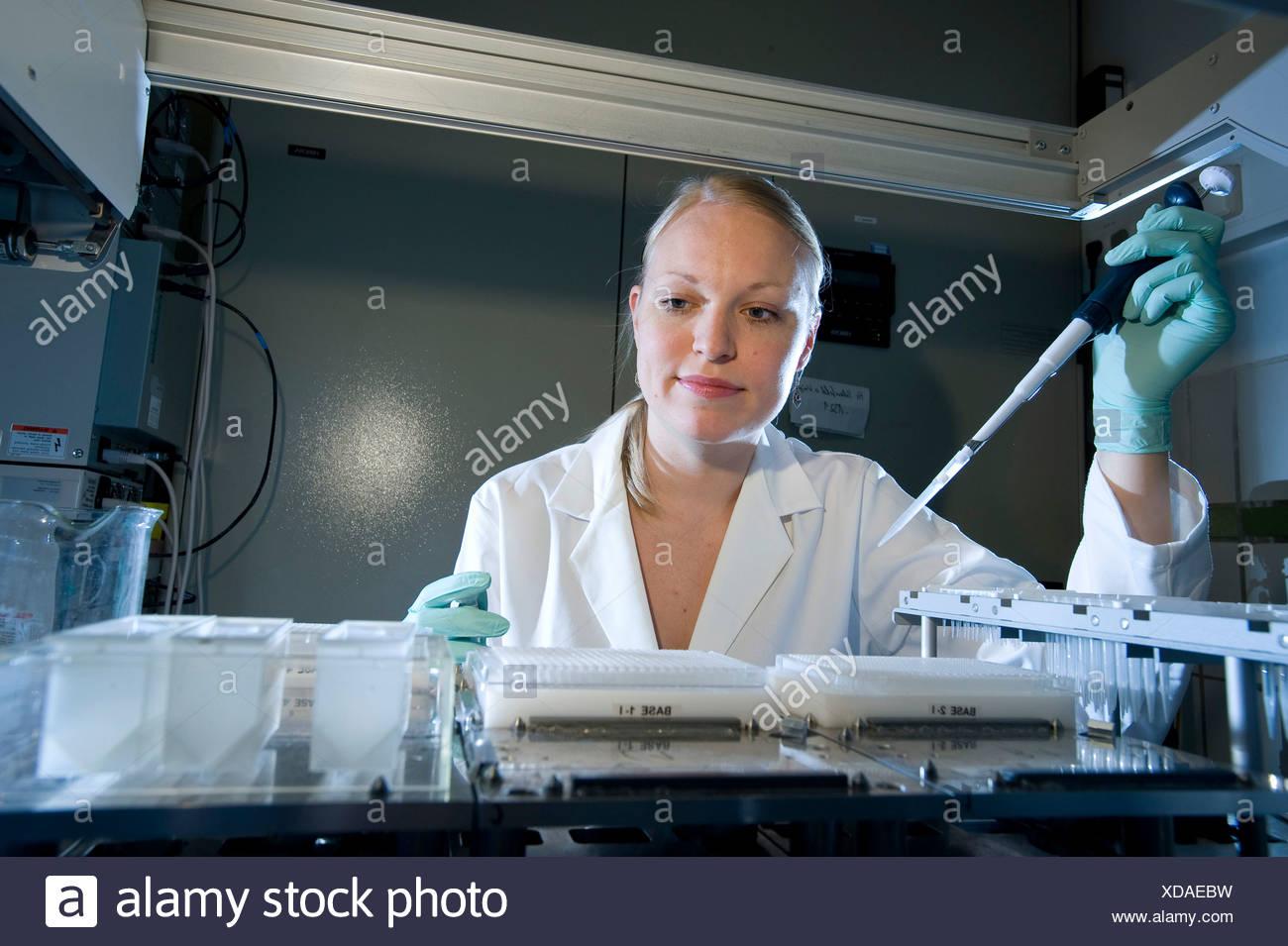 Weibliche Laborantin mit einem Pipettierroboter, Max-Planck-Institut für molekulare Genetik, AG Kardiovaskulaere Genetik Stockbild