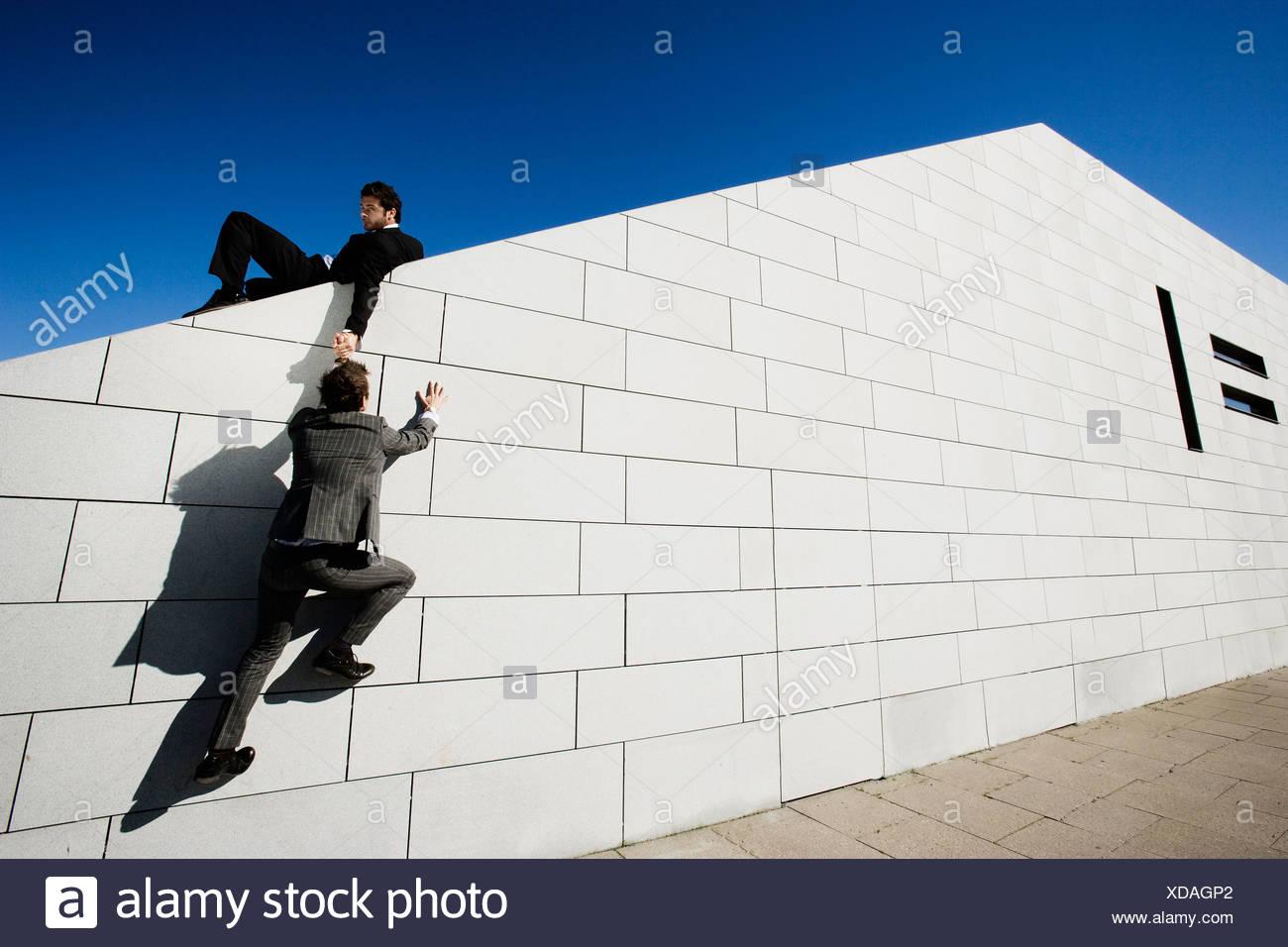 Menschen Anderen Menschen Helfen Uber Mauer Stockfotografie Alamy