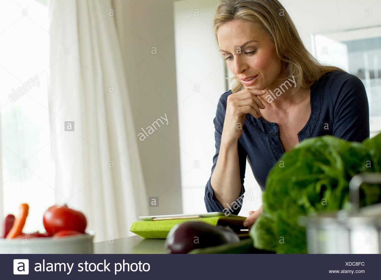 Reife Frau mit digital-Tablette Stockbild