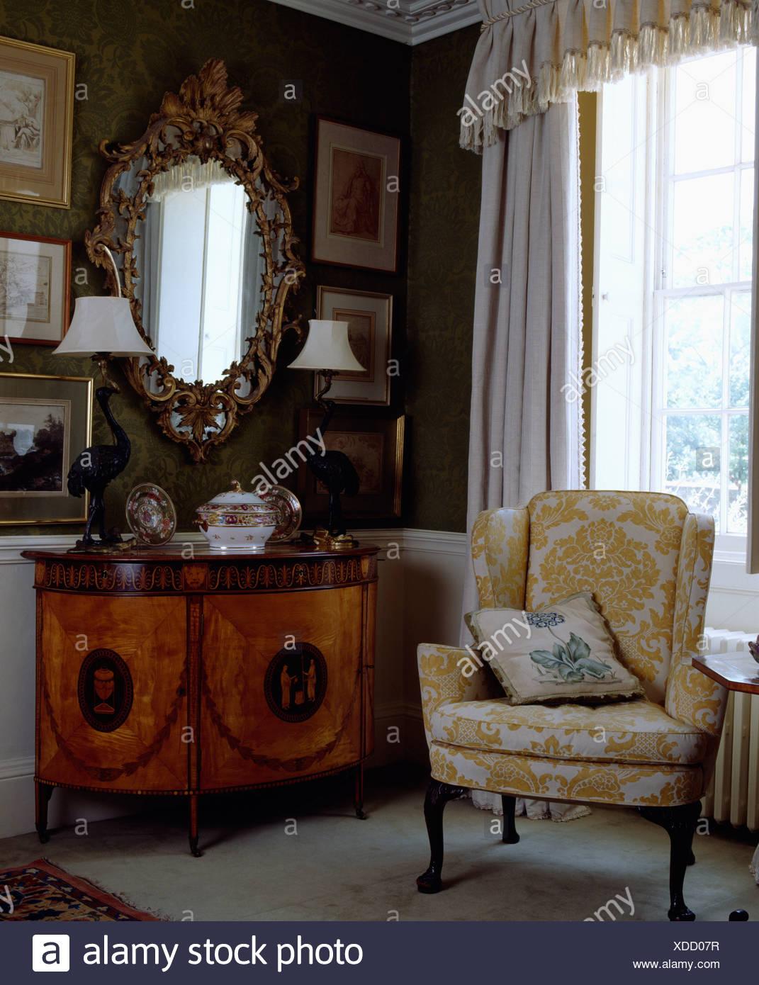 Gepolsterte Sessel neben Biedermeier Schrank im Wohnzimmer ...