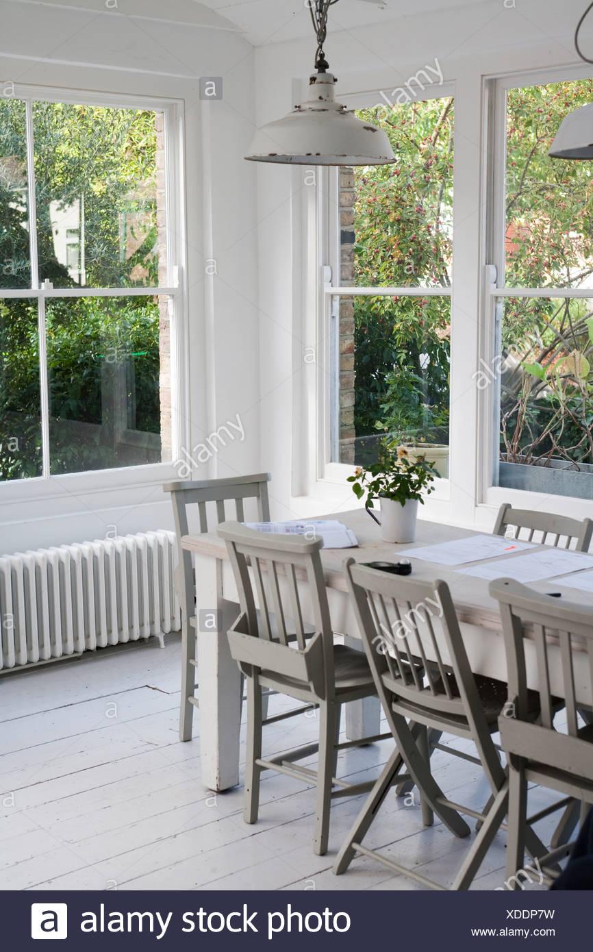 Einfache weiße Esszimmer mit Tisch und Stühlen von windows Stockbild