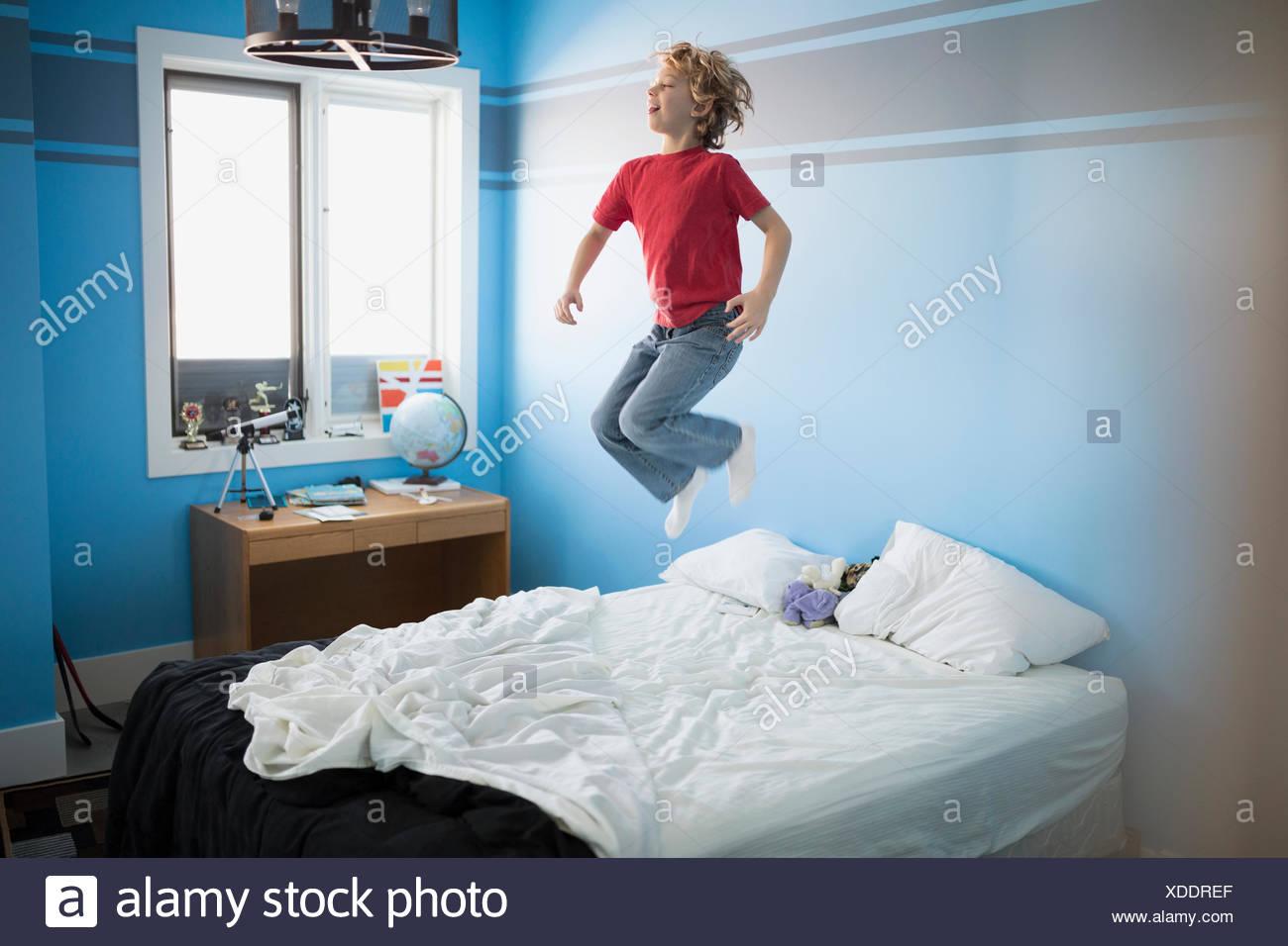 Junge, springen auf Bett Stockbild