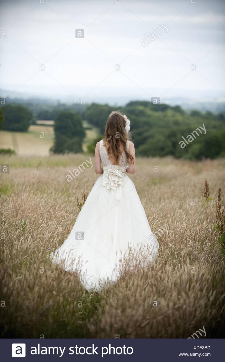 Eine Braut in ihrem Hochzeitskleid stehend in einem Feld-England Stockbild