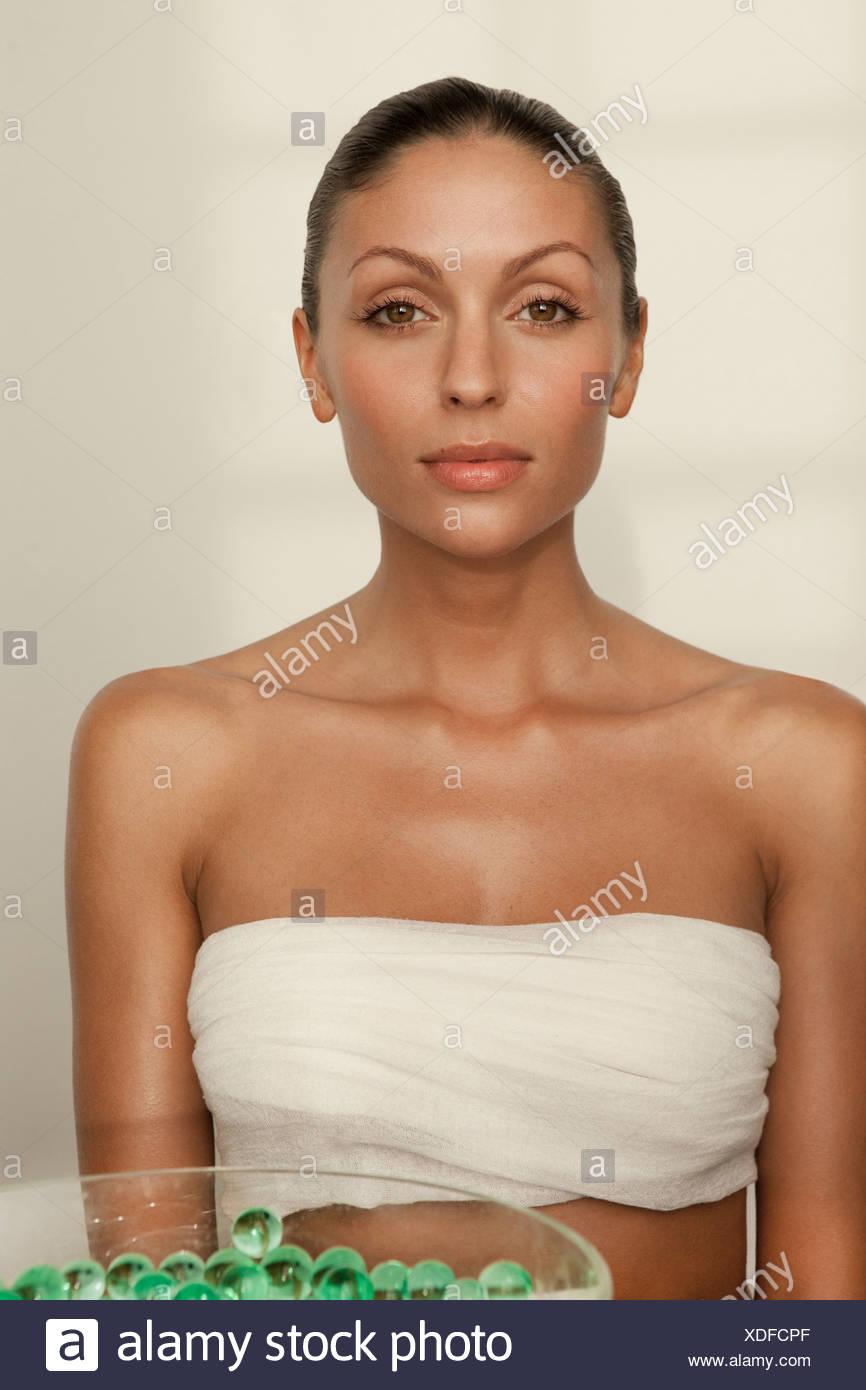 Frau sitzt mit Schüssel mit Glasperlen Stockbild