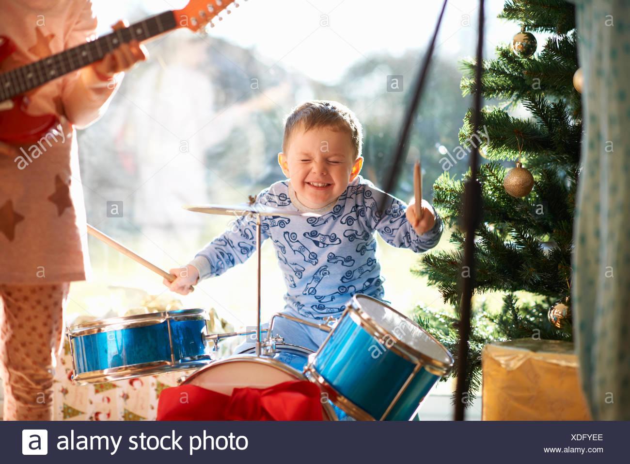 Junge und Schwester spielen Spielzeug Schlagzeug und Gitarre am Weihnachtstag Stockfoto