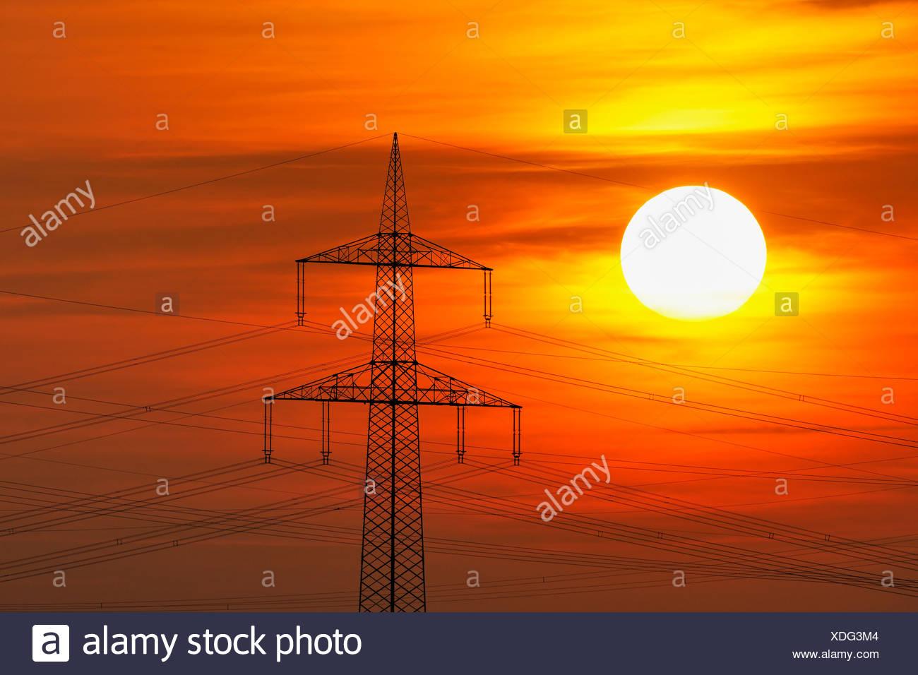 Elektrische Hochspannungsleitungen, Strommasten, mit der untergehenden Sonne, Beinstein in der Nähe von Stuttgart, Baden-Württemberg Stockbild
