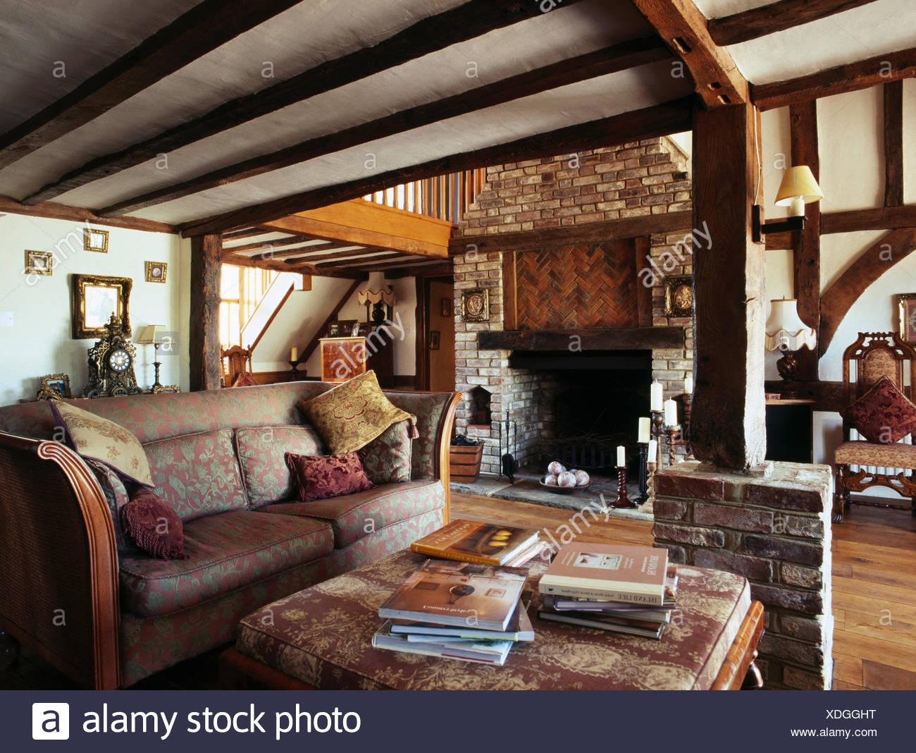 gemusterten sofa im wohnzimmer mit gemauerten kamin und holzbalken
