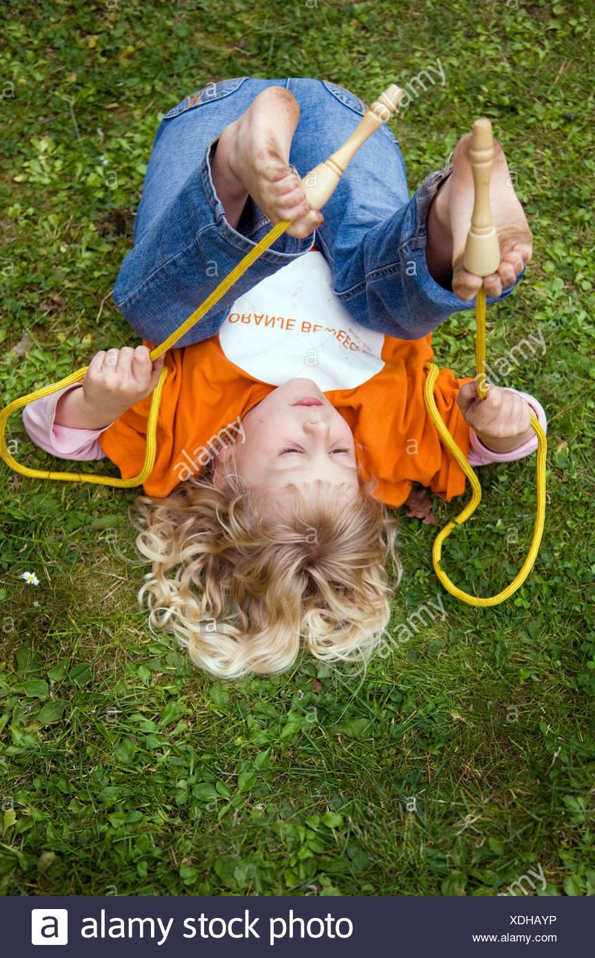 Berlin, Mädchen spielen mit einem Springseil auf dem Rasen Stockbild