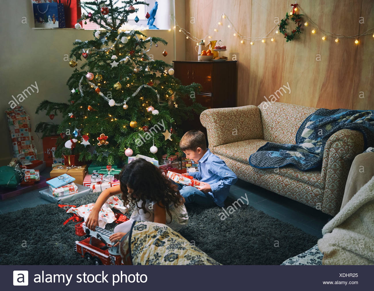 Family Unwrapping Gifts Christmas Tree Stockfotos & Family ...