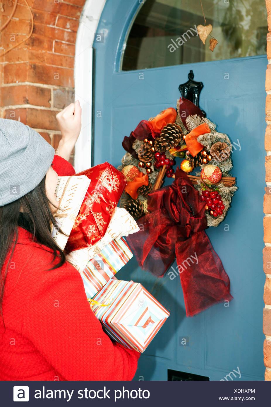 Frau mit verpackte Geschenke an Haustür Stockbild