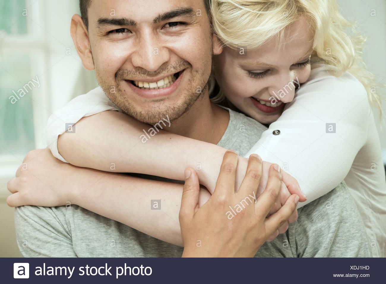Junge Frau umarmt Freund Stockbild