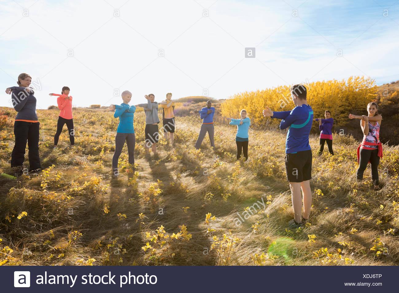 Stretching im sonnigen ländlichen Bereich Gruppenfitness Stockbild