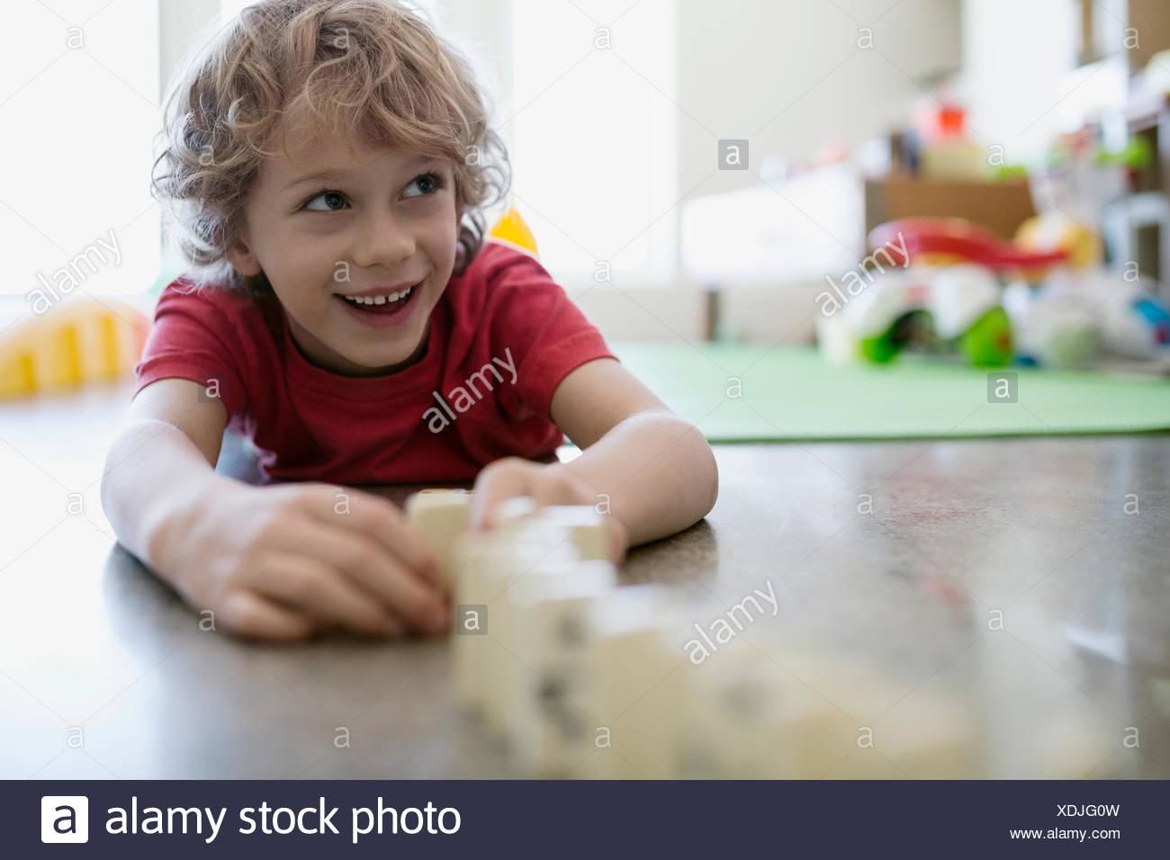 Lächelnde junge spielt mit Dominosteinen Erdgeschoss Stockbild