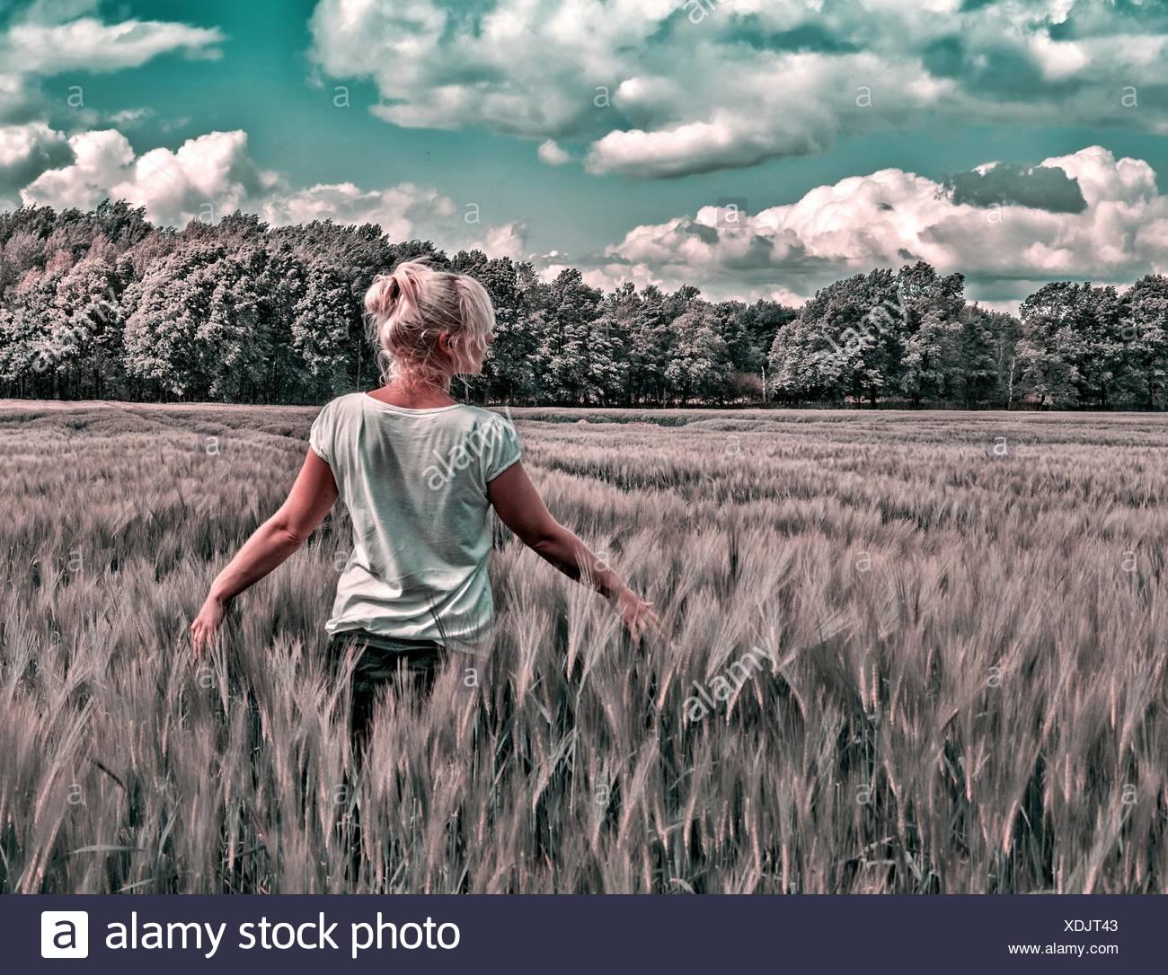Rückansicht der Frau auf landwirtschaftlichen Bereich gegen Himmel Stockbild