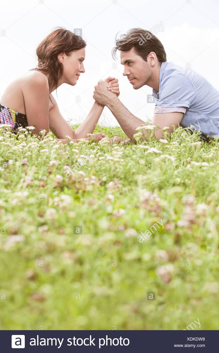 Profil-Bild von paar Armdrücken beim liegen auf dem Rasen gegen Himmel Stockbild