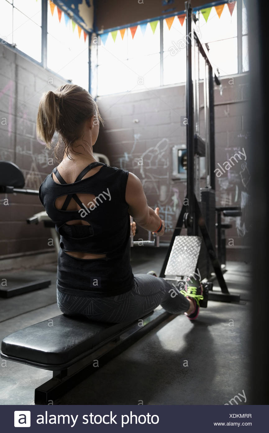Frau Gewichtheben, sitzende Zeilen in düstere Turnhalle zu tun Stockbild