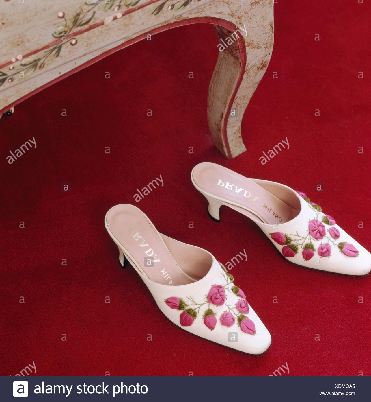 1f1a2a4792d7e Nahaufnahme der weiße Prada Schuhe mit Rosa Seide Rosen appliziert Stockbild