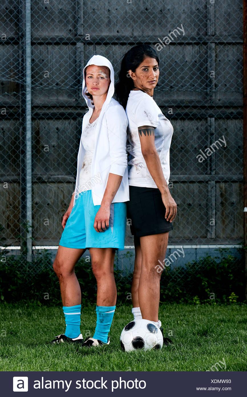 zwei weibliche Fußball-Spieler stehen Rücken an Rücken Stockbild
