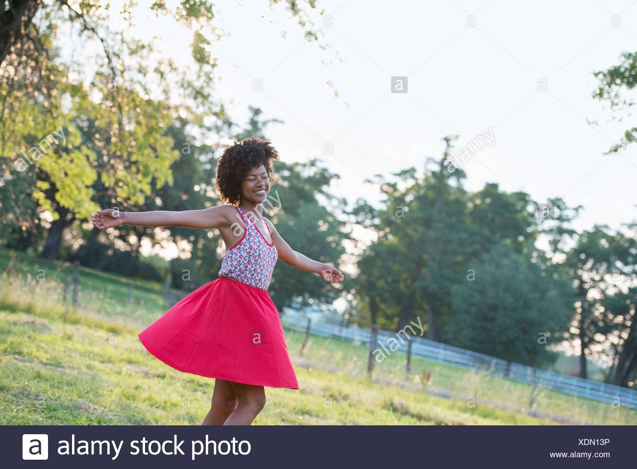 Eine Frau in einem roten Rock, wirbeln um unter freiem Himmel, mit ausgestreckten Armen. Stockbild