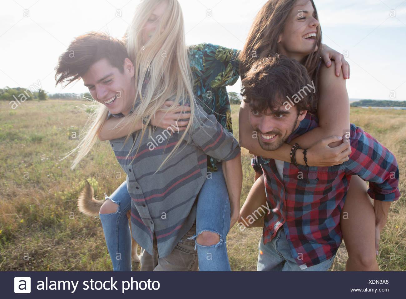 Junge Männer, Frauen, die Piggy backs Stockbild