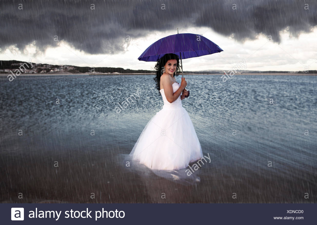 Braut mit Schirm im Regen Stockbild