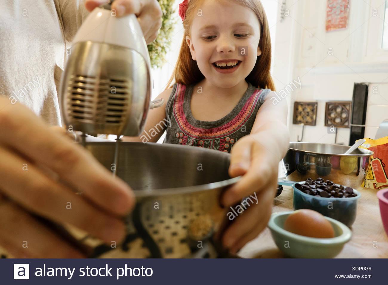 Mädchen, Mutter eine helfende hand in Küche Stockfoto