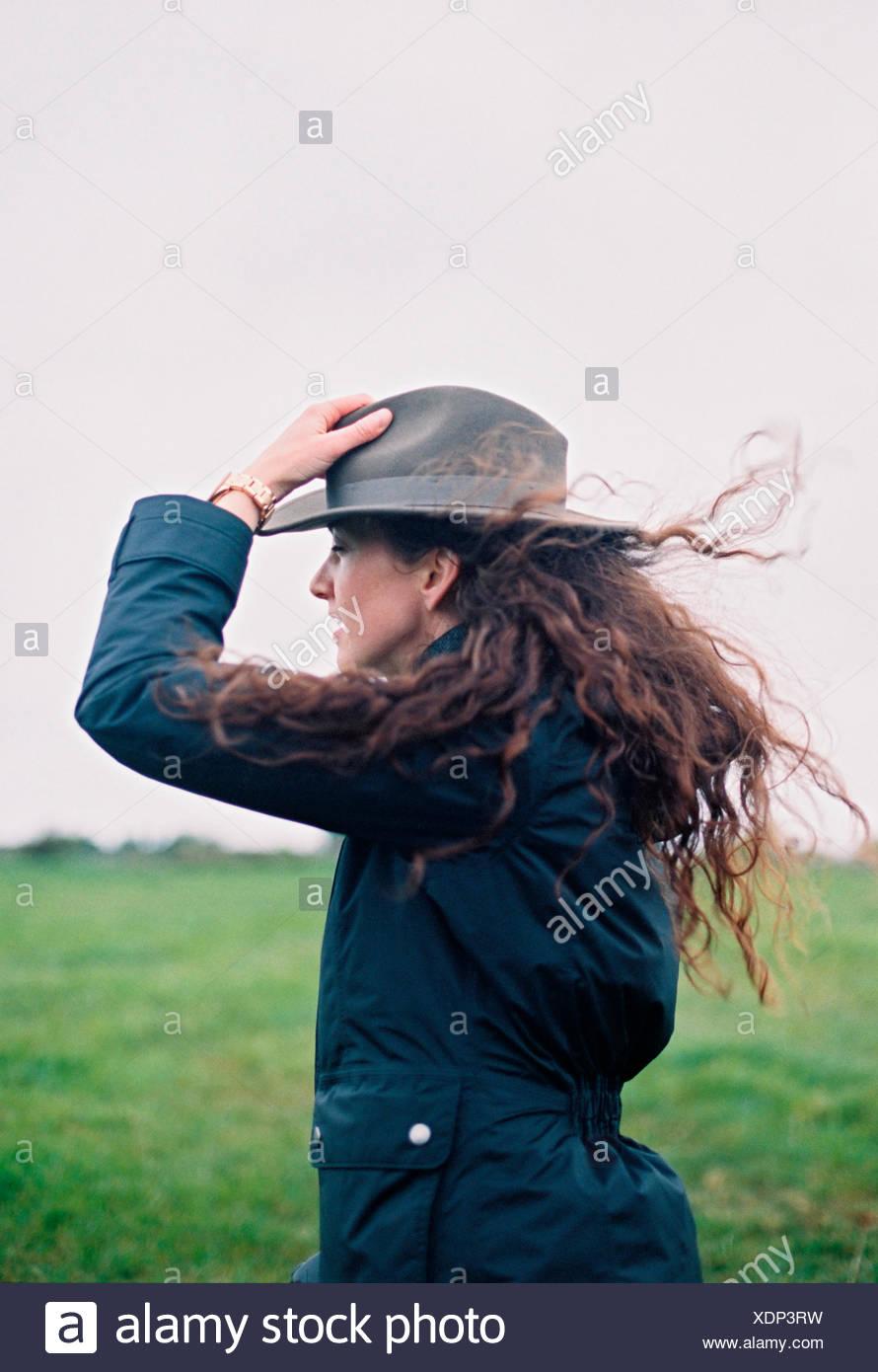 Eine Frau mit langen Haaren im Wind geblasen mit ihrem Hut. Stockbild
