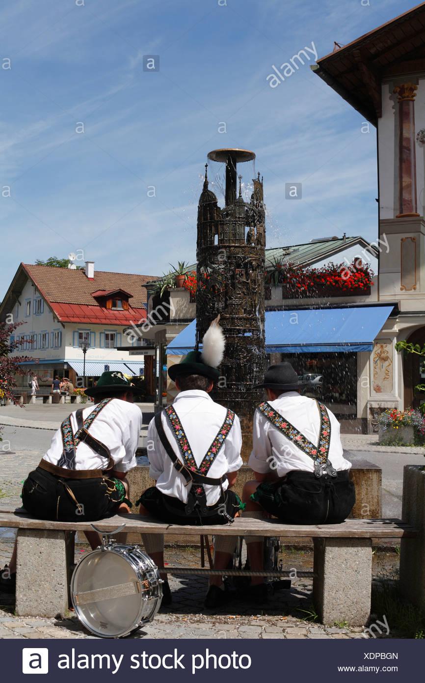 Drei junge Männer tragen traditionelle Lederhosen vor dem Brunnen auf Dorfstrasse, Oberammergau, Oberbayern, Deutschland, E Stockbild