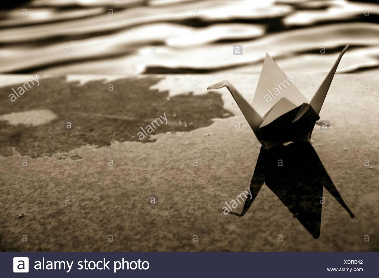 Papierkranich auf Sims durch Fluss Stockbild
