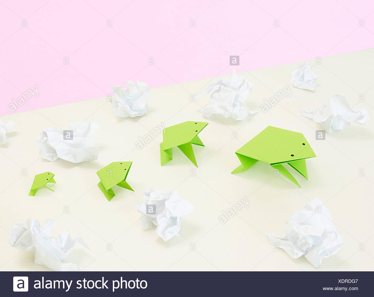 Origami-Frösche inmitten zerquetscht Papier Stockbild