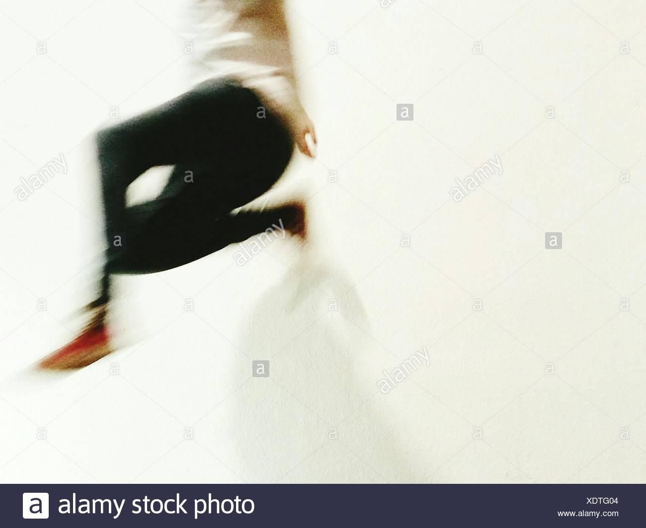 Verschwommenes Bild der Person springen vor weißem Hintergrund Stockbild