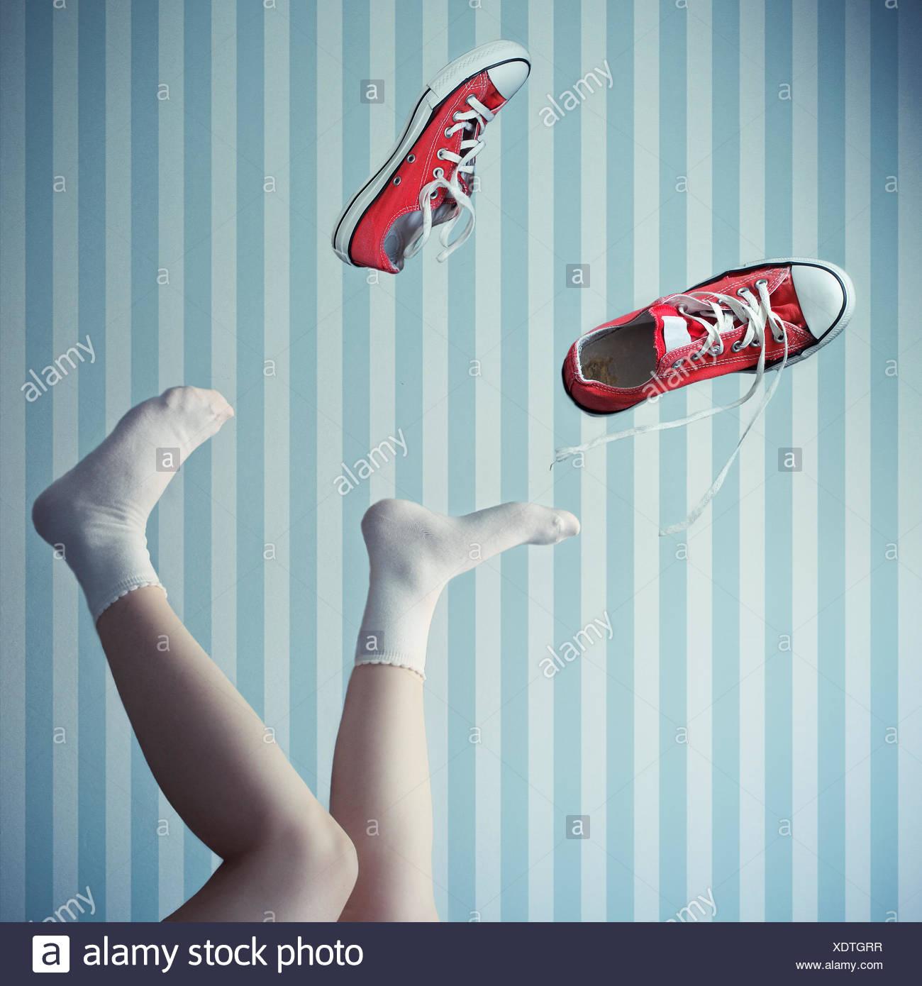 Frau mit ihren Beinen in der Luft mit Trainer Mitte Luft Stockbild