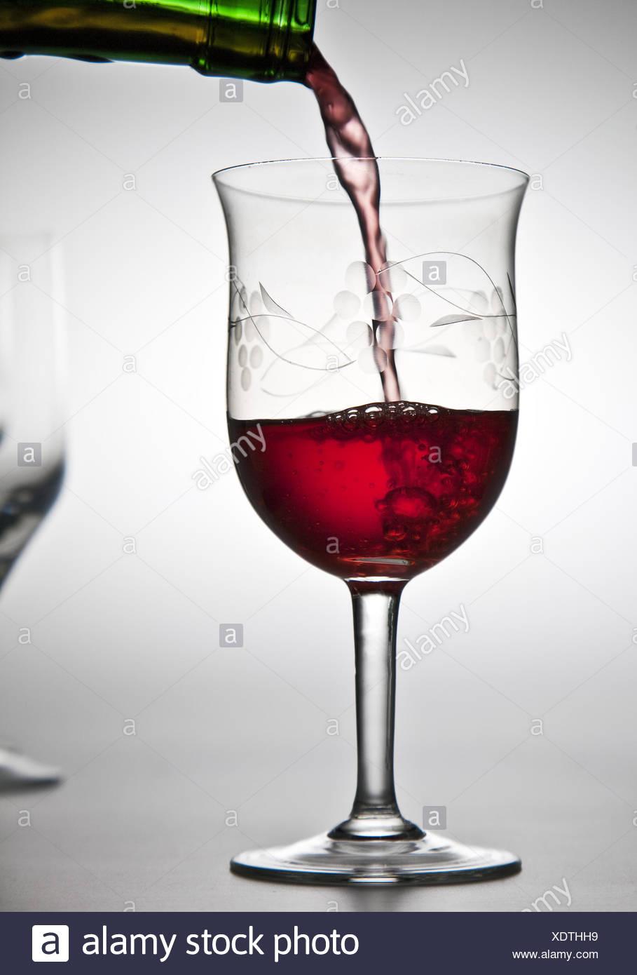 Rotwein wird in ein Glas gegossen Stockbild