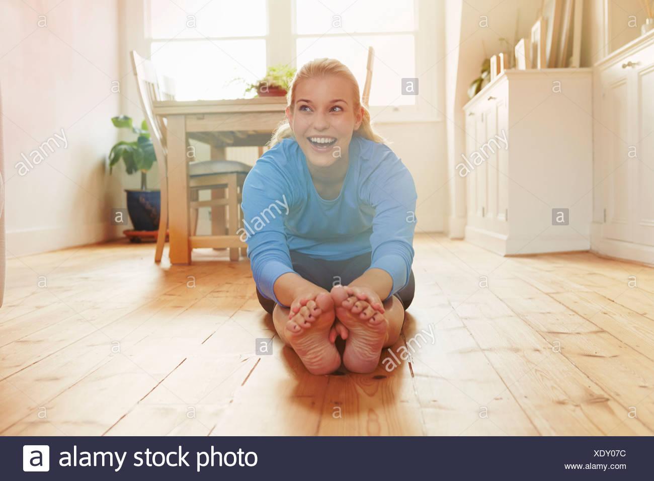 Junge Frau sitzt am Boden schiefe Zehen nach vorne berühren Stockbild