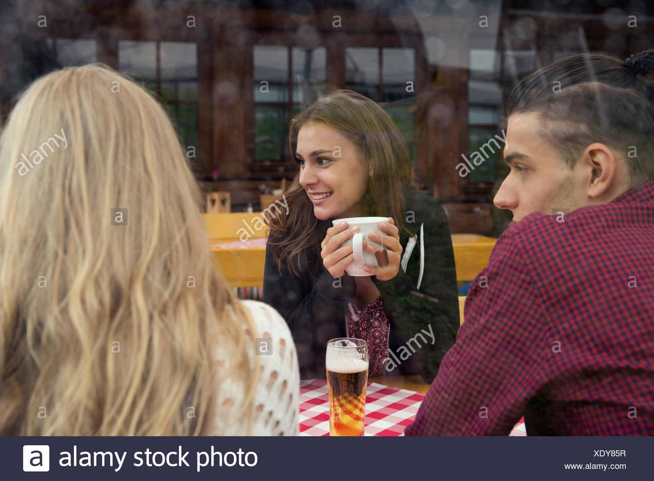 Drei junge Erwachsene Freunde mit Kräutertee und Bier im café Stockfoto