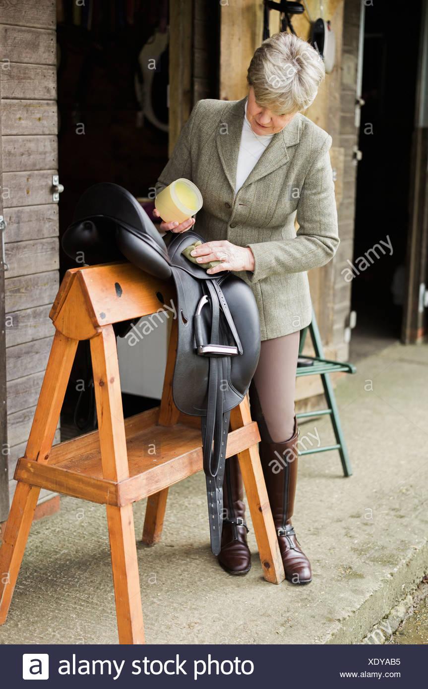 Eine Frau, Reinigung und Vorbereitung Tack und Sattel im Hof des einen Reitstall. Stockbild