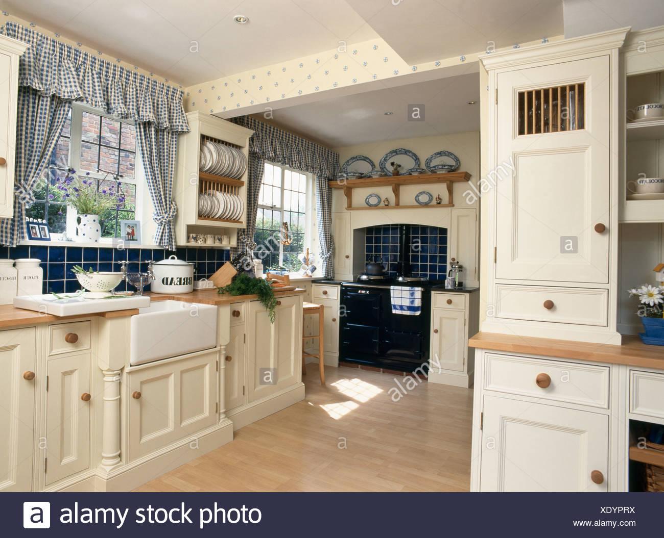 blaue aufgegebenes vorh nge am fenster im landhaus k che mit eingebauten creme einheiten und. Black Bedroom Furniture Sets. Home Design Ideas