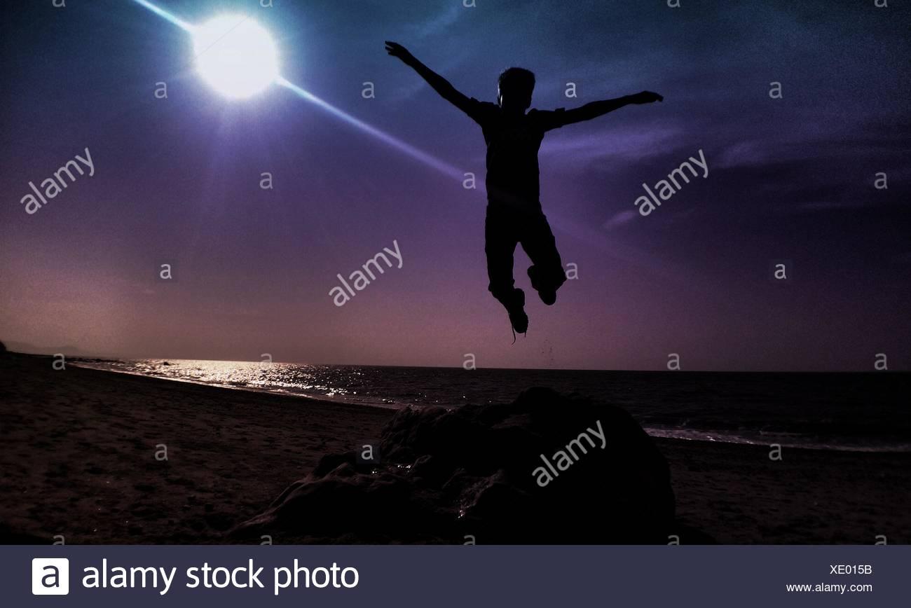 Silhouette-Mann springt am Strand gegen Bright Sun Stockbild