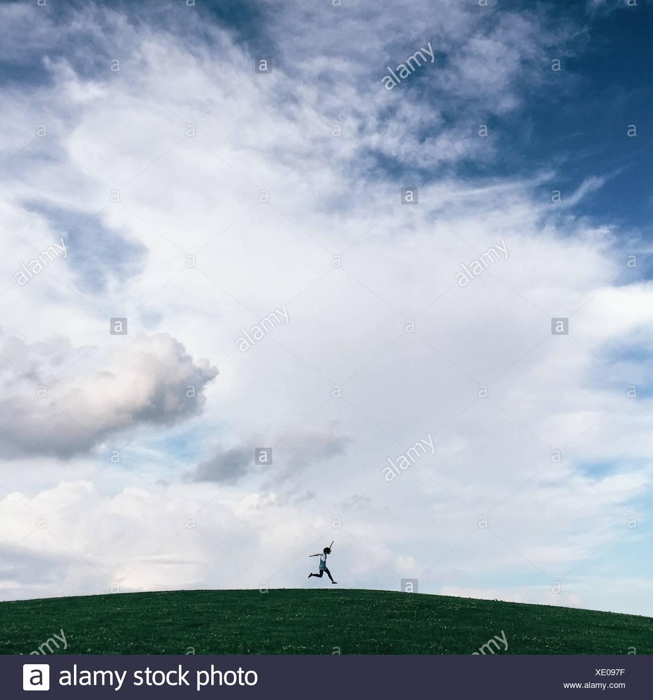 Niedrigen Winkel Sicht der Person auf grasbewachsenen Hügel gegen bewölktem Himmel springen Stockbild
