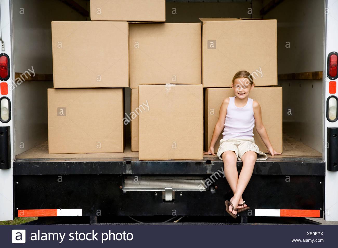 Kleines Mädchen sitzt mit Kartons in der Entfernung Van Umzug Stockbild