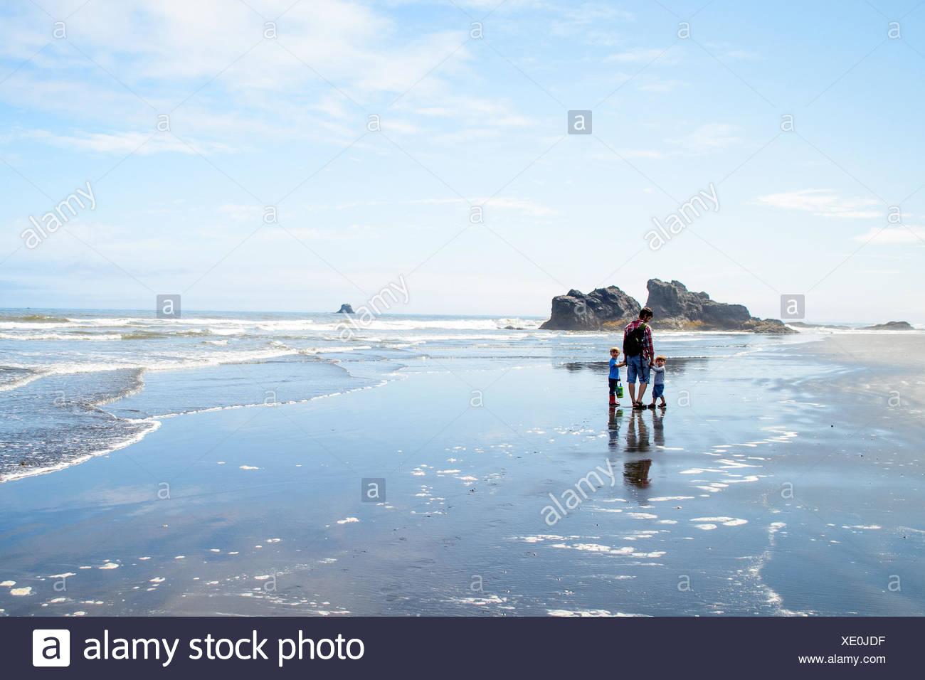 Mutter mit zwei Kindern (2-3, 4-5) stehen am Strand Stockbild