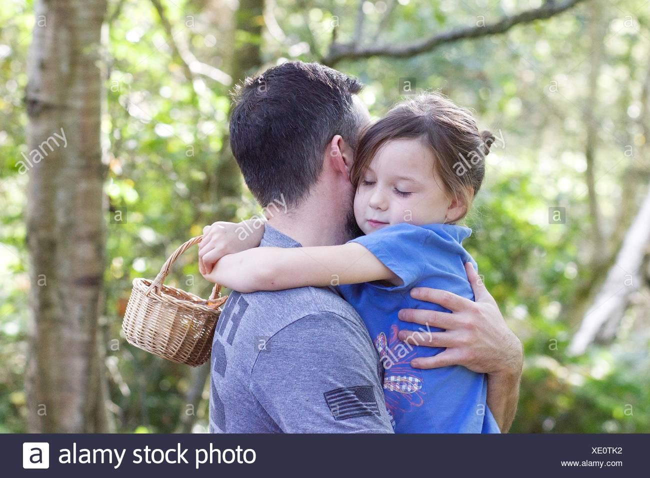 Mädchen stehen im Wald ihren Vater umarmt Stockbild