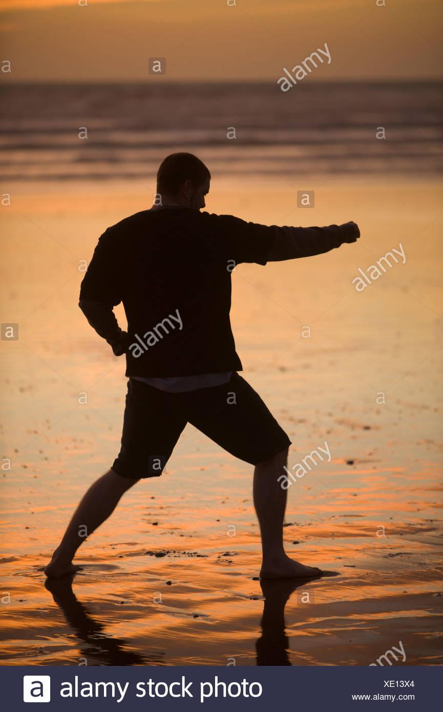 Eine Mitte erwachsener Mann praktiziert Taekwondo am Strand bei Sonnenuntergang in Morro Bay, Kalifornien. Stockbild