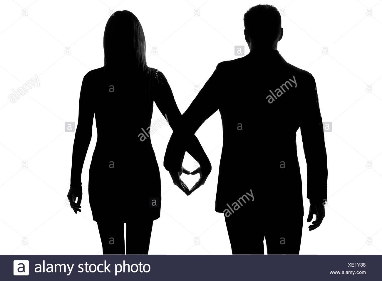 ein liebhaber kaukasischer paar mann und frau gehen hand in hand studio silhouette isoliert auf. Black Bedroom Furniture Sets. Home Design Ideas