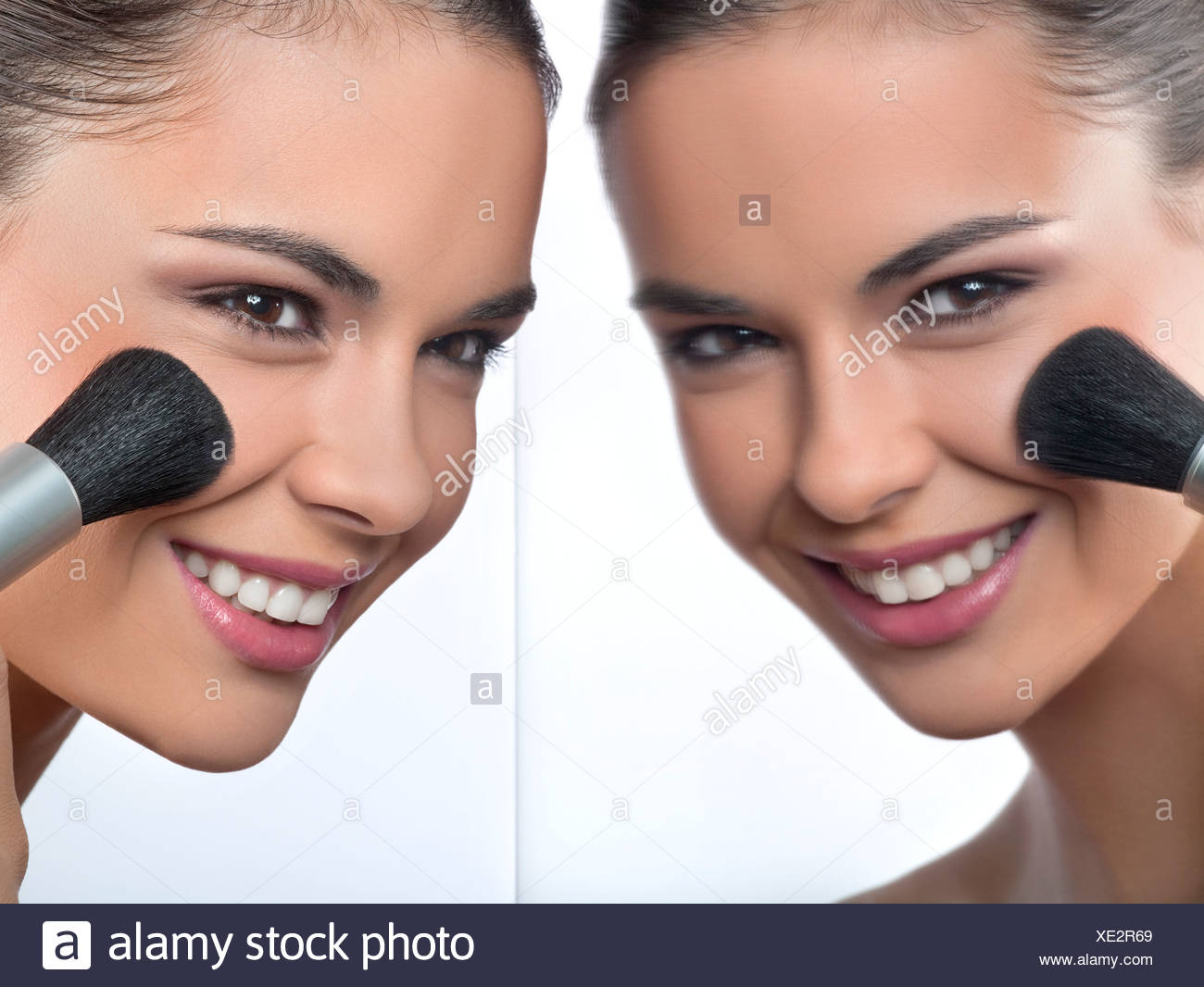 Junge Frau, die Anwendung von erröten und ihre Reflexion im Spiegel Stockbild