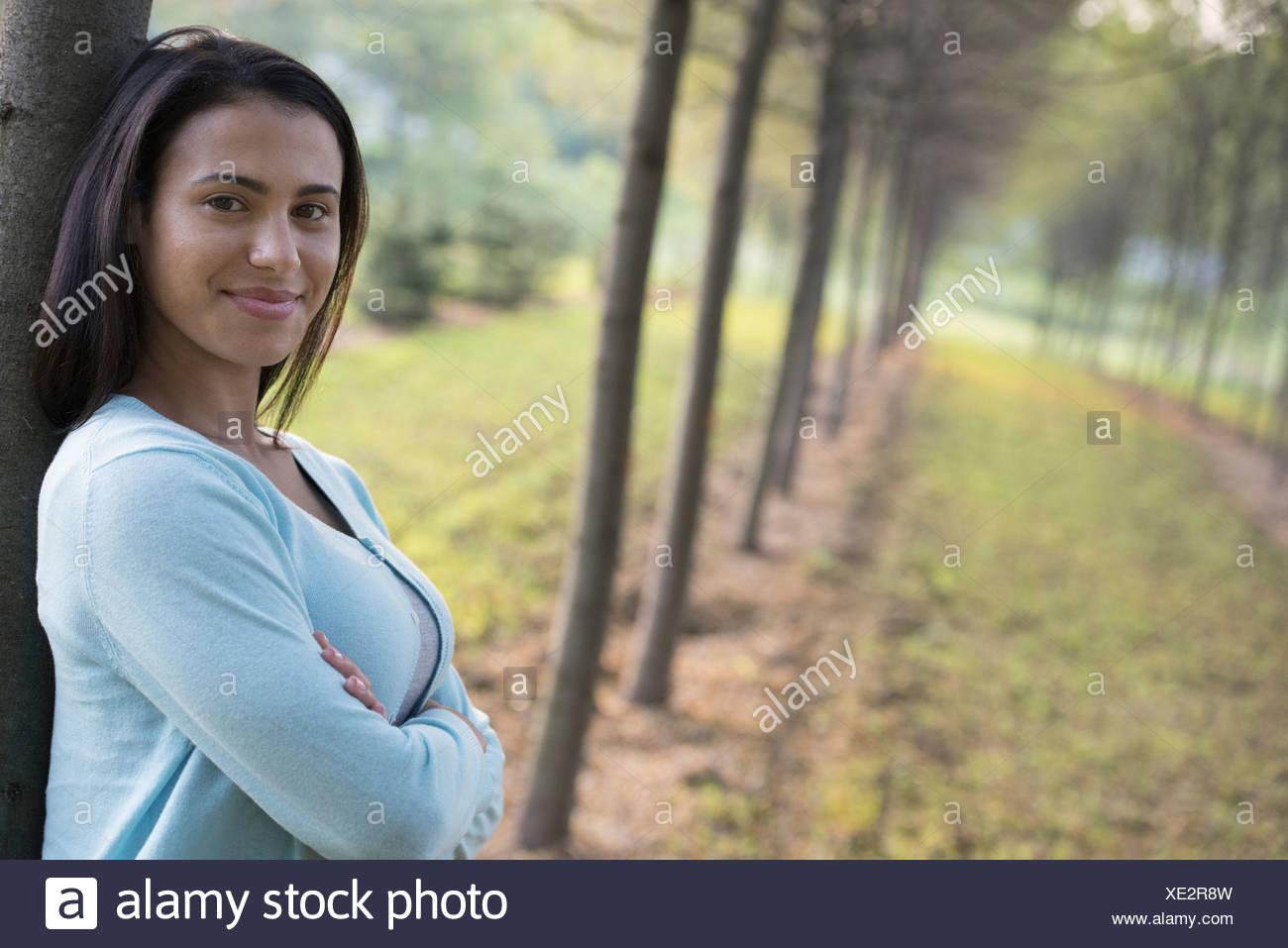Eine Frau mit Armen gefaltet an einen Baum gelehnt. Stockbild