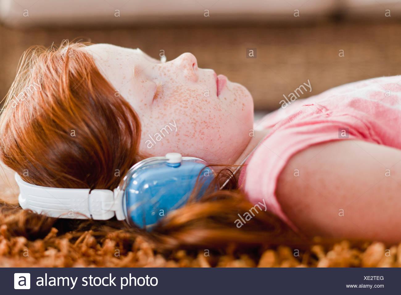 Mädchen hören Kopfhörer auf Teppich Stockfoto