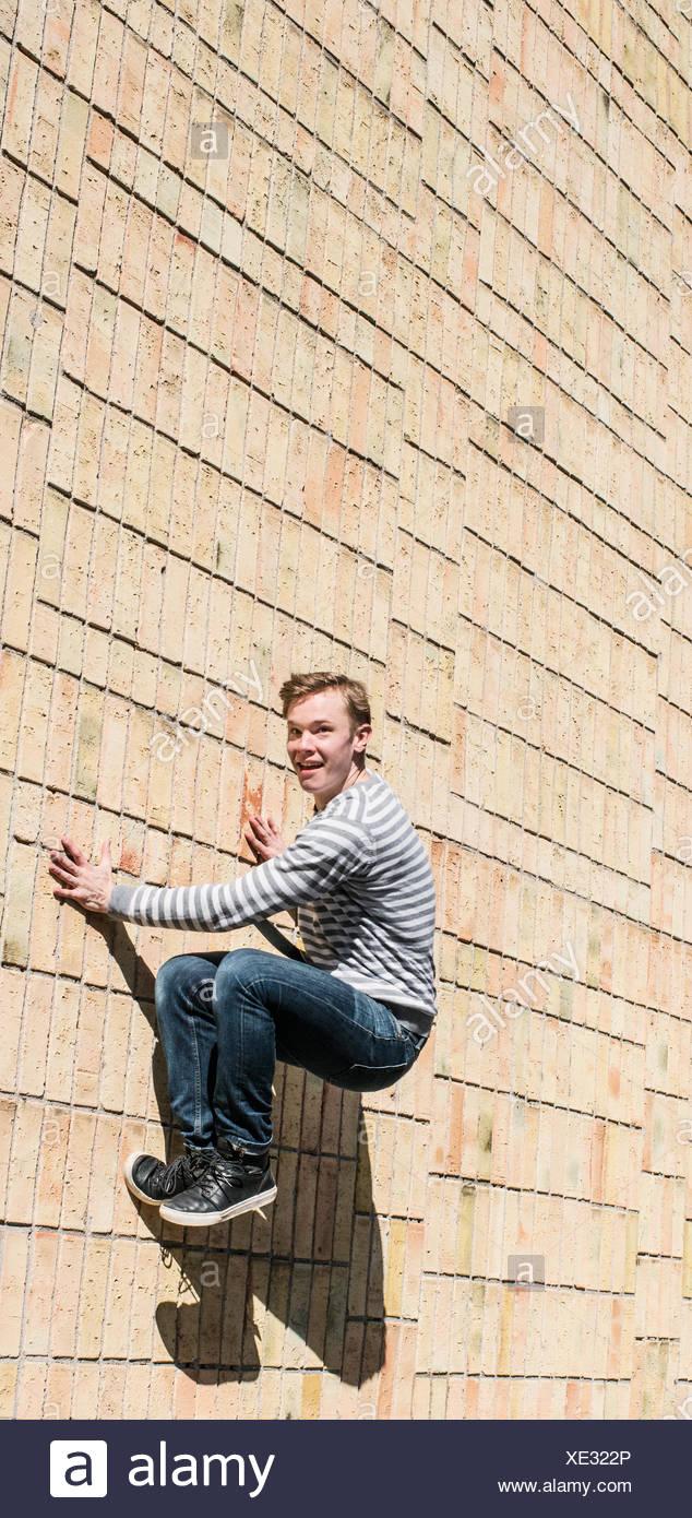 Junger Mann tun parkour Sprung auf Mauer, Schweden Stockbild