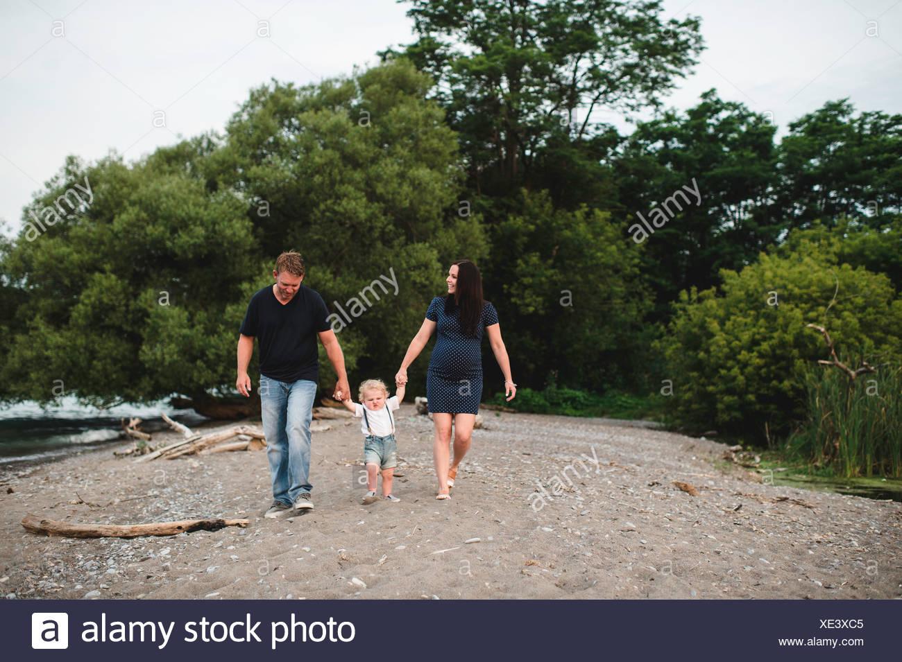 Schwangeren Paare schlendern am Strand mit männlichen Toddlersohn, Lake Ontario, Kanada Stockbild