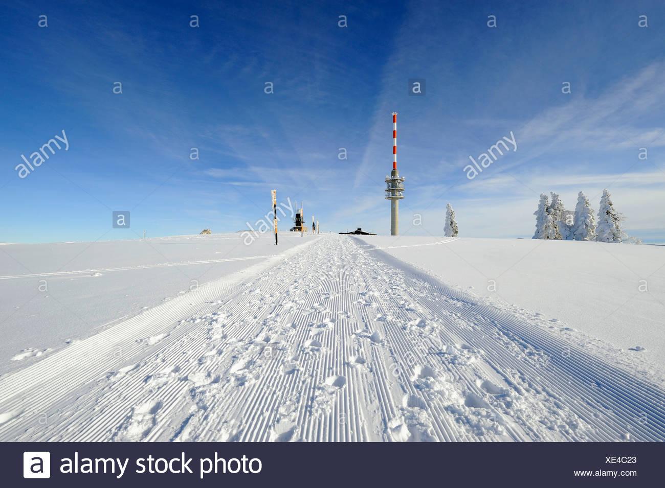 Gewalzten Schnee trail auf dem 1493m hohen Mt. Feldberg im Schwarzwald, am Horizont die neue Feldbergturm-Antenne mit der Stockbild